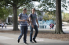 Two young male students walking on-campus.