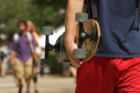 Student walks to class with skateboard.