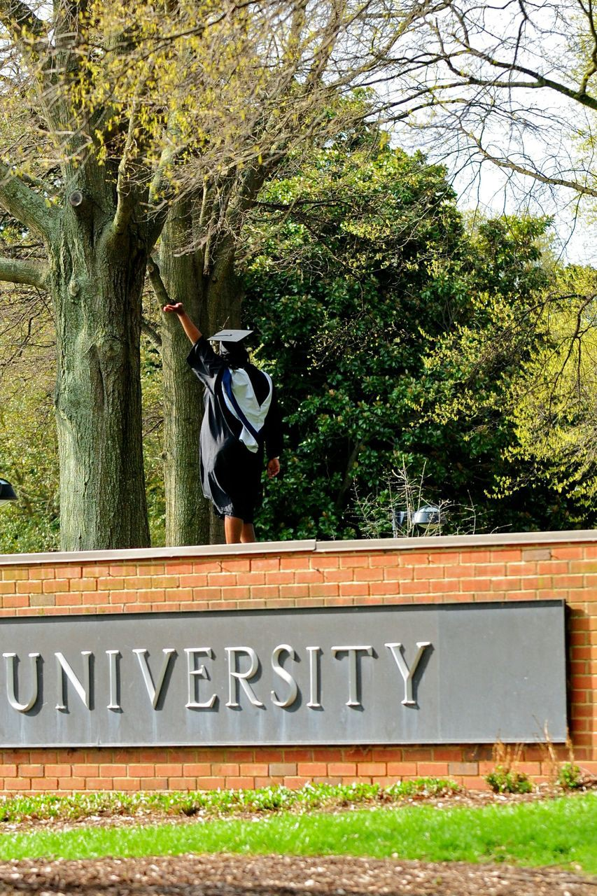 across the campus a photo essay  a spring graduate poses for an early memento photo atop the sign at the east end