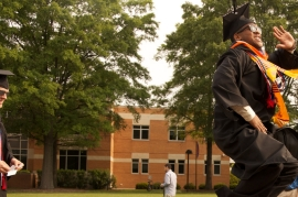 A graduate enthusiastically jumps on the University Seal during the processional at spring commencement 2013